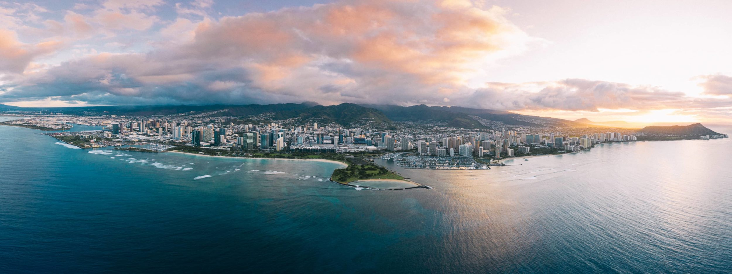 Aerial photo of Honolulu with ocean, mountains, and buildings