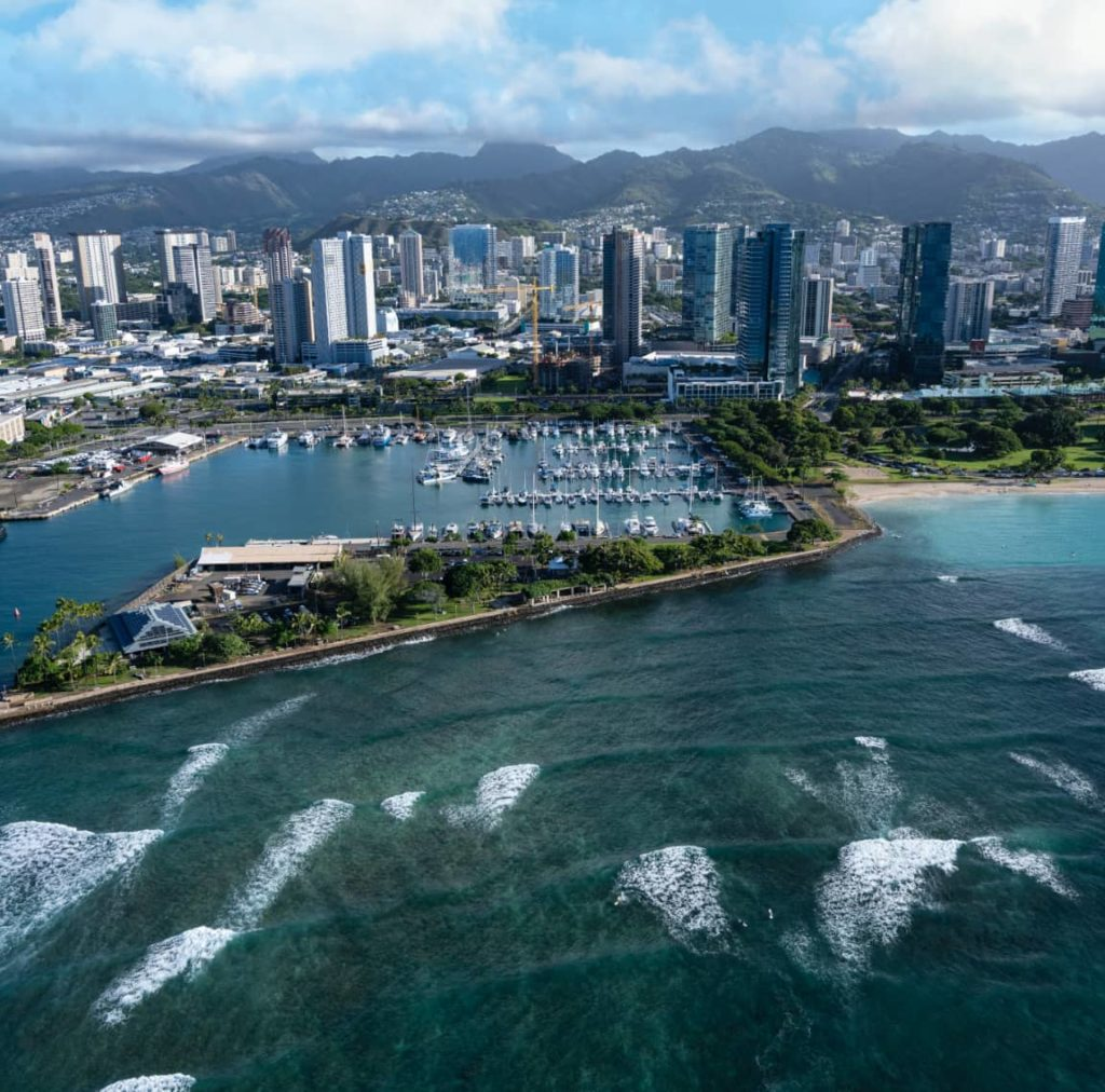 Aerial photo of a Honolulu harbor, ocean, mountain, and buildings