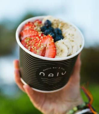 Nalu Health acai bowl topped with strawberries, blueberries, bananas and bee pollen